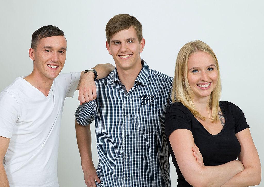 Zwei junge Männer und eine junge Frau mit verschränkten Armen lächeln in die Kamera.
