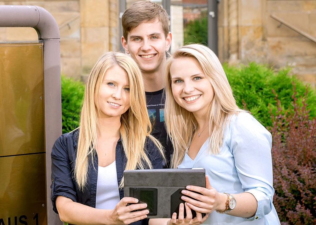 zwei Studentinnen und ein Student schauen mit einem Tablet in der Hand in die Kamera.