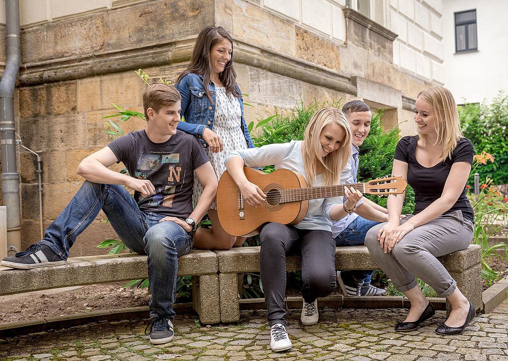 eine Gruppe von Studenten sitzen auf einer Bank und lauschen einer Musikerin mit Gitarre