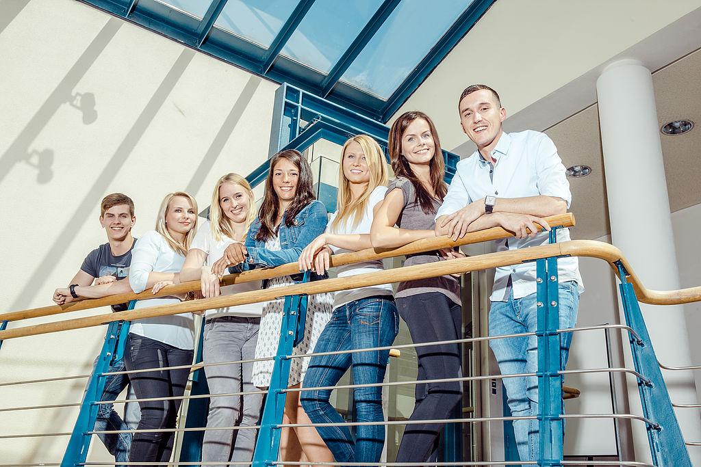 eine Gruppe von Studenten steht am Treppengeländer und schaut nach unten in die Kamera.