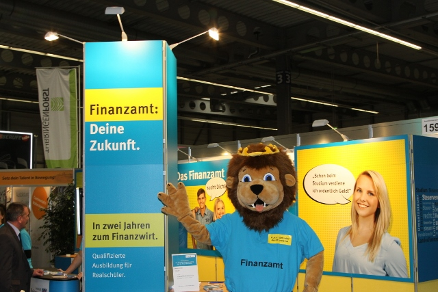 Person mit Löwenkostüm steht vor dem Messestand der Thüringer Steuerverwaltung