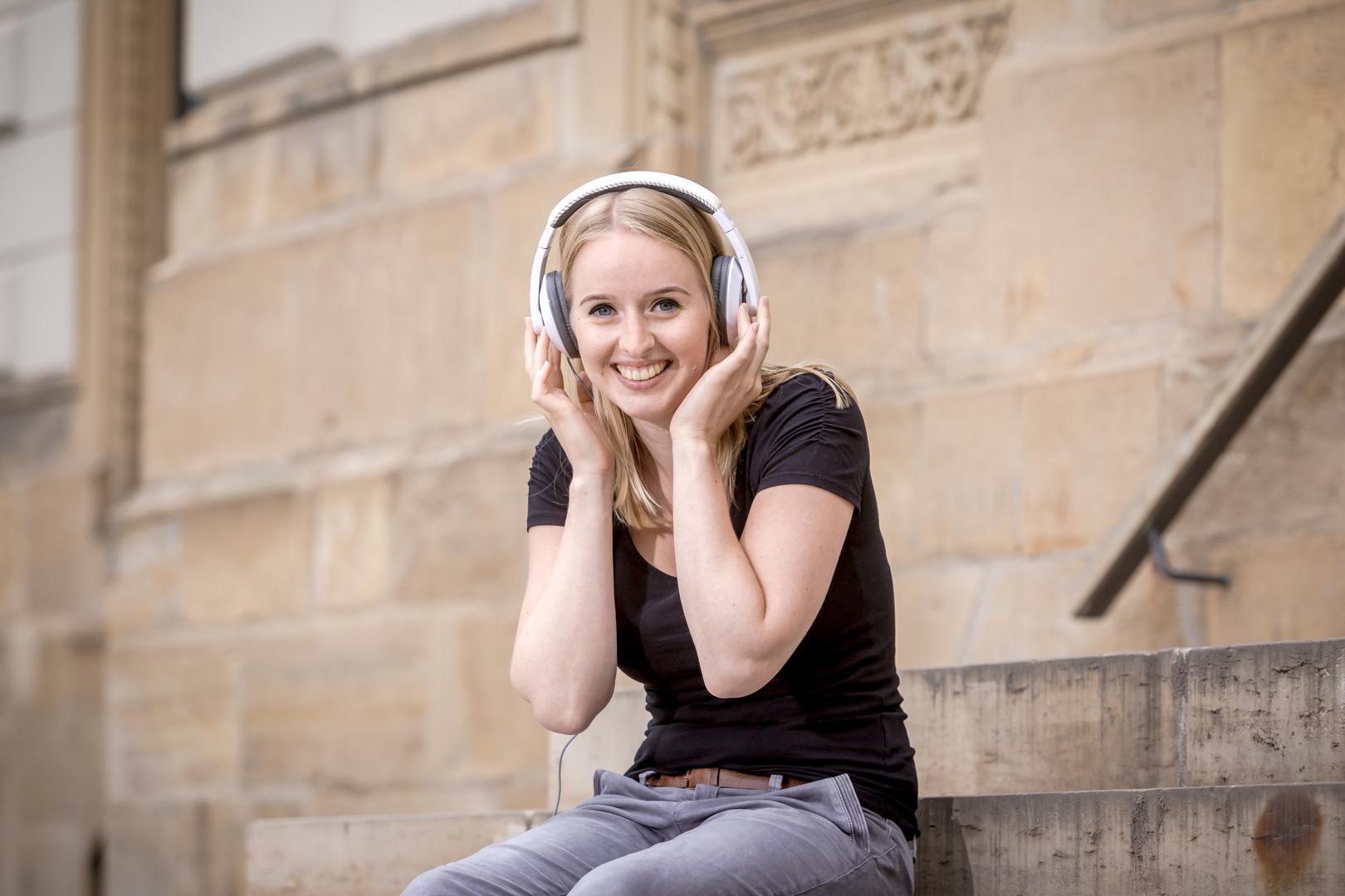 Junge Frau sitzt mit Kopfhörern aud der Treppe und lächelt in die Kamera.