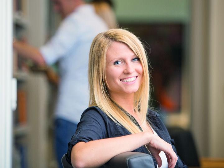 junge Frau sitzt am Schreibtisch und lächelt in die Kamera